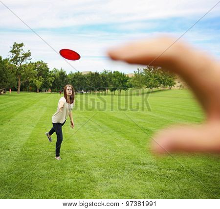 woman in the background throwing a disc to a hand in the foreground of the frame