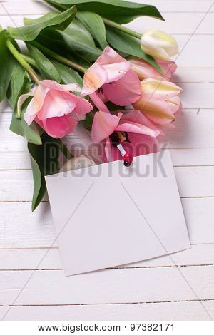 Bunch Of Fresh  Spring  Pink  Tulips And Empty Tag  On White  Painted Wooden Background.