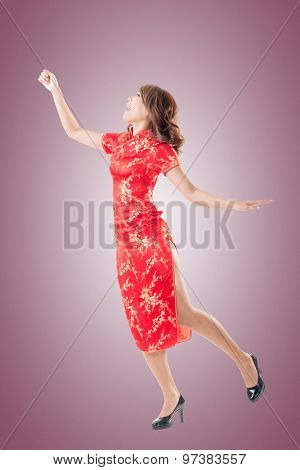 Smiling and excited Chinese woman dress traditional cheongsam at New Year, studio shot isolated.
