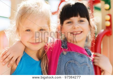 summer, childhood, leisure, friendship and people concept - group of happy little girls on children playground climbing frame