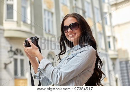tourism, travel, leisure and holidays concept - smiling teenage girl with digital camera taking picture on city street