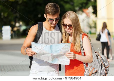 travel, tourism, summer vacation and people concept - smiling couple with map and backpack looking for location in city