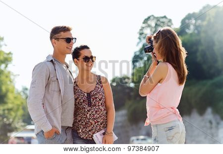 friendship, tourism, summer, technology and people concept - happy friends with camera taking picture outdoors