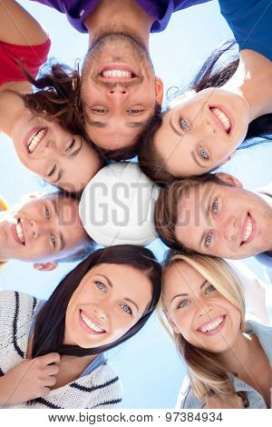 friendship, summer holidays, sport and people concept - group of smiling friends with beach ball standing in circle over blue sky