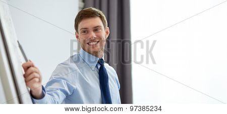 business and people concept - smiling businessman pointing marker to flipboard on presentation in office