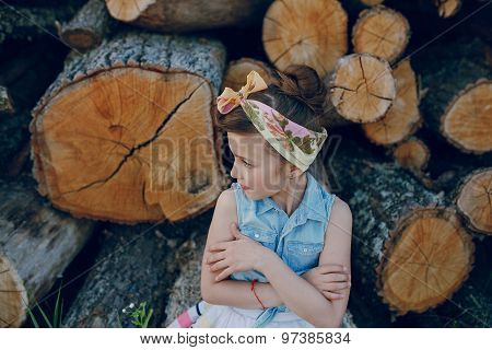 beautiful little girl sitting on trees