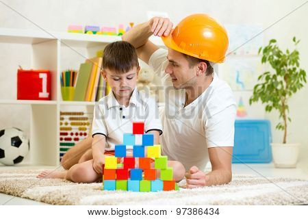 Father and child play construction game together at home.