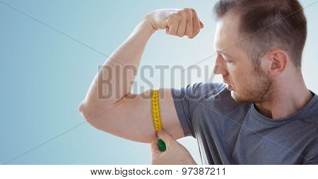 sport, fitness, bodybuilding and people concept - close up of male hands with tape measuring bicep over blue background