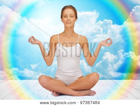 people, health, wellness and meditation concept - woman in underwear meditating in yoga lotus pose on wooden floor over white clouds and rainbow on blue sky background