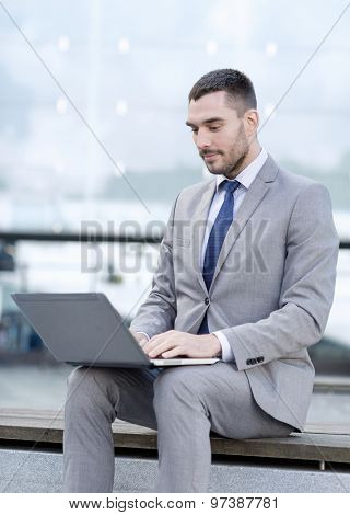 business, education, technology and people concept - businessman working with laptop computer on city street