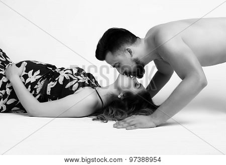 Husband Kissing Pregnant Wife Lying On The Floor