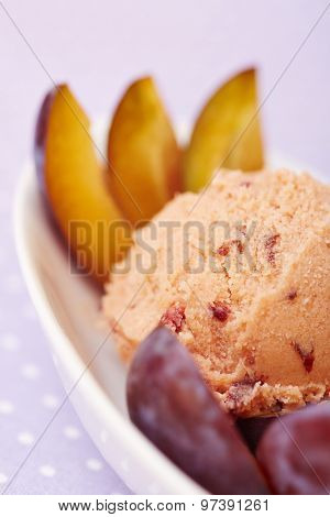 A scoop of homemade plum ice cream with fresh plums