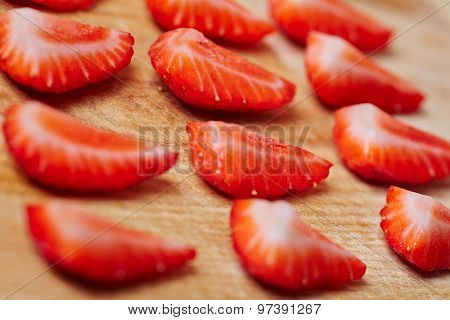 Quarted fresh strawberries assorted on a wooden board