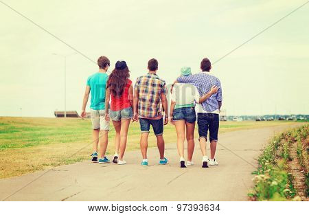 holidays, vacation, love and friendship concept - group of teenagers walking outdoors from back