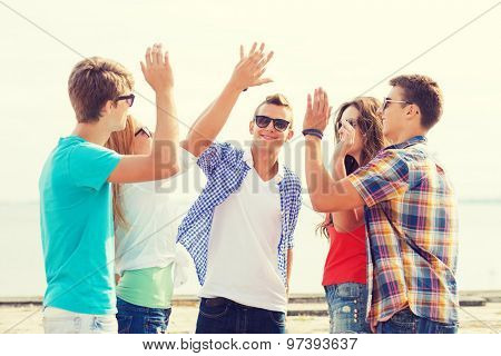 friendship, leisure, summer, gesture and people concept - group of smiling friends making high five outdoors