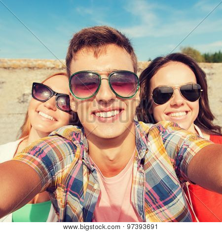 friendship, leisure, summer, technology and people concept - group of smiling friends taking selfie outdoors