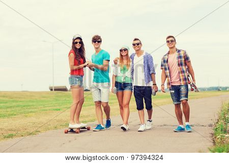holidays, vacation, love and friendship concept - group of smiling teenagers walking and riding on skateboards outdoors
