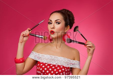 Surprised Woman with makeup brushes.   She is standing against a pink background.