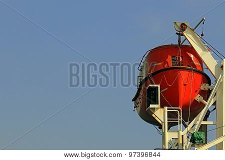 rescue boat red on the davits of a ship on the background of blue sky