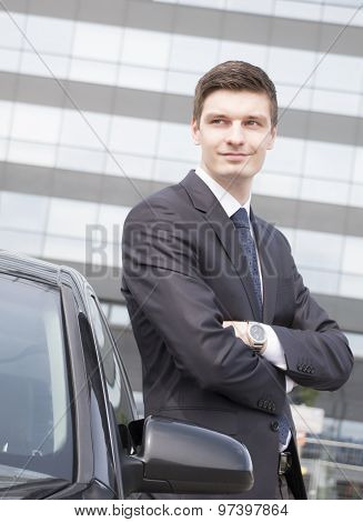 Handsome young businessman near his car