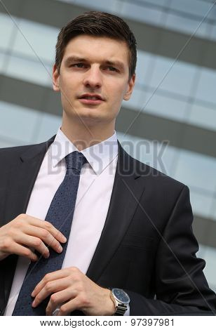 Handsome young businessman sitting in his car