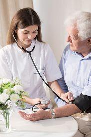 stock photo of hypertensive  - Senior man with hypertension having measured blood pressure - JPG