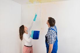 foto of leak  - Young Woman With Bucket Showing Water Leaking From Damage Ceiling To Maintenance Guy - JPG