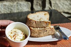 foto of home-made bread  - serving of bread on a white plate with a butter knife and home made butter - JPG