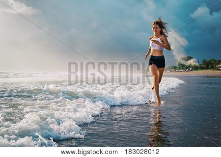 poster of Active sporty woman run along ocean surf by water pool to keep fit and health. Sunset black sand beach background with sun. Woman fitness jogging training and sport activity on summer family holiday.