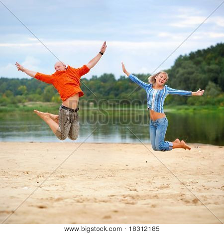 Boy And Girl Jump On Beach