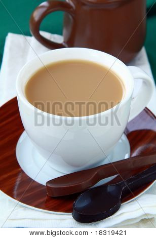 tea with milk in a white cup with chocolate dessert spoons