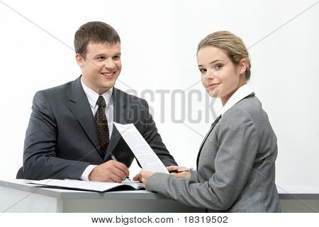 Photo of friendly secretary sitting at table and looking at camera with her partner near by