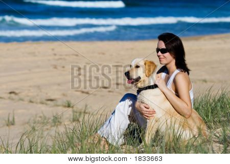 Young Female Sitting On A Beach With A Dog
