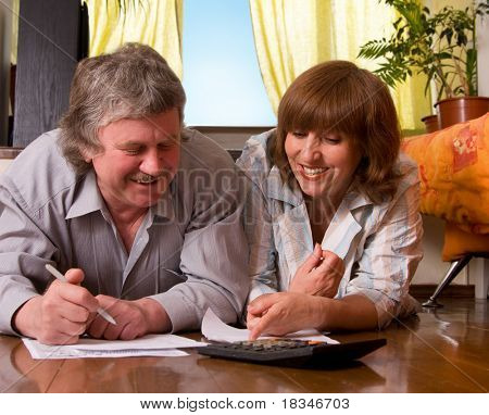 Happy mature couple with documents at home