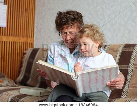 Grandmother reading book to the granddaughter at home