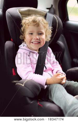 Happy girl in an automobile carseat