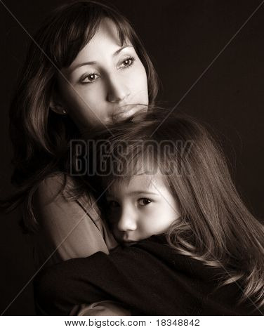Sad mother and daughter on black