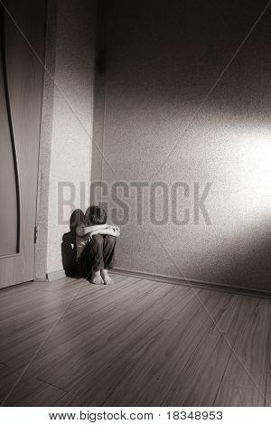 Kind sitzt in einer Zimmer-Ecke