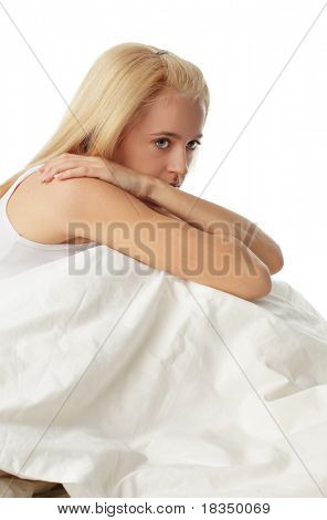 Worried young woman on bed