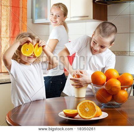 Feliz madre con hijos jugo de naranja exprimido
