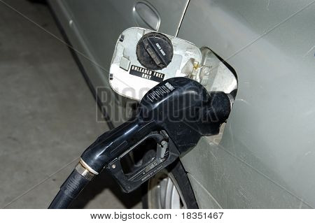 A gray automobile at a gas station pumping gas