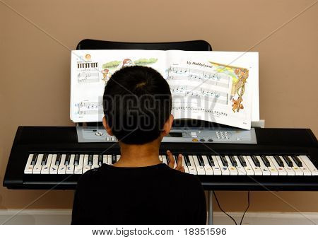 young hands playing on a key board