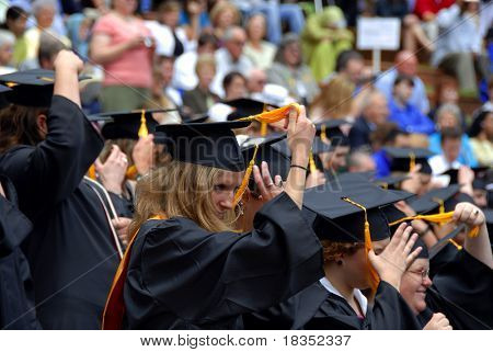 A row of womens graduating and ready to change their hats
