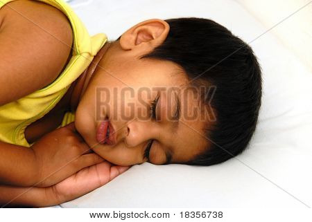 An young kid lying in bed feeling very sick