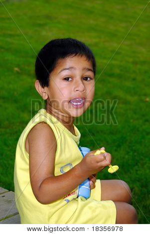 An handsome Indian kid blowing bubbles in the park