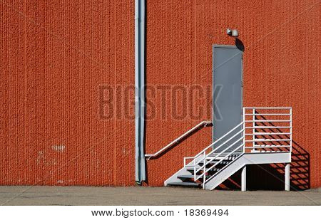 stair to backdoor against red patterned wall