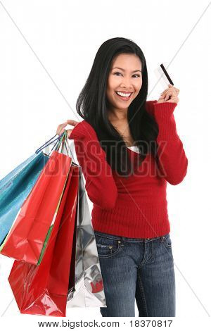young smiling asian female holding shopping bags and credit card