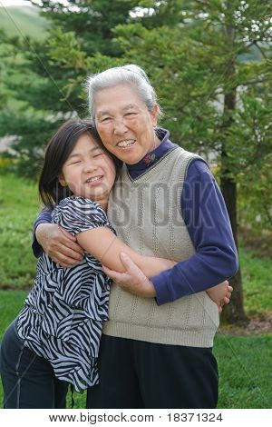 Grandma and Grand Daughter Hug Each Other Outdoor