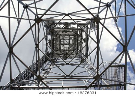 metal structure  of antenna mast under sky with clouds