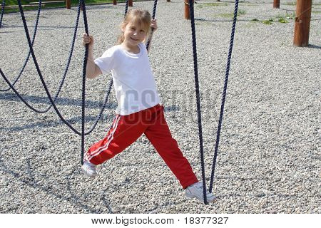 young girl playing on rope swing